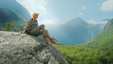 The-Tourist-Sits-On-A-Large-Rock-Surrounded-By-High-Mountains-Alone-Amidst-The-Incredibly-Beautiful-