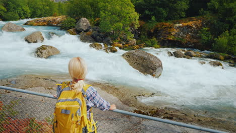 A-Young-Woman-Stands-By-The-Fence-Looks-At-The-Rugged-Mountain-River-Meltwater-Runs-From-The-Briksda