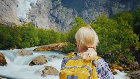 A-Woman-Traveler-Looks-At-The-Famous-Briksdal-Glacier-In-Norway-A-Back-View