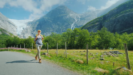 An-Active-Successful-Woman-Travels-Through-Norway-Walks-Against-The-Backdrop-Of-Mountains-With-A-Bac