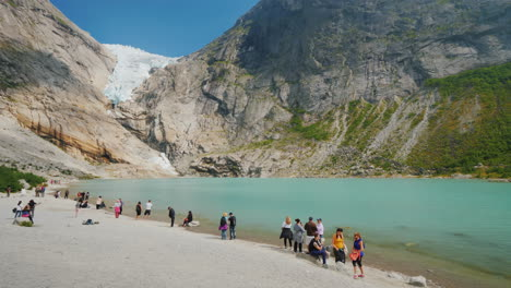 Tourists-Stroll-By-The-Lake-Formed-From-The-Meltwater-Of-The-Brixdal-Glacier