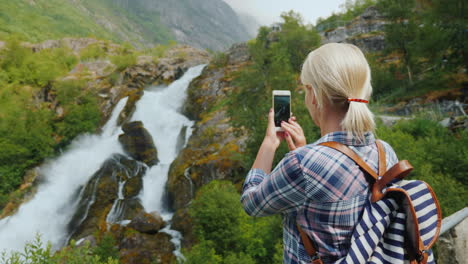 Female-Traveler-Takes-Pictures-Of-A-Picturesque-Waterfall-In-Norway-Briksdal-Glacier-The-Majestic-Sc