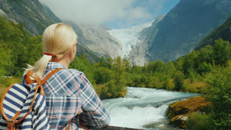 A-Female-Traveler-Looks-At-The-Beautiful-Mountains-And-Glacier-On-Top-Briksdal-Glacier-In-Norway-The