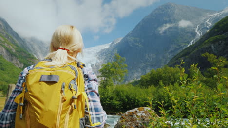 A-Tourist-With-A-Yellow-Backpack-Looks-At-A-Beautiful-Glacier-At-The-Top-Of-The-Mountain-Briksdal-Gl