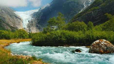 Clear-Water-In-A-Mountain-Stream-Against-The-Background-Of-A-Glacier-In-The-Mountains-Briksdal-Glaci