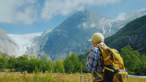 An-Active-Woman-With-A-Backpack-Walks-Against-The-Backdrop-Of-The-Mountains-And-The-Briksdal-Glacier