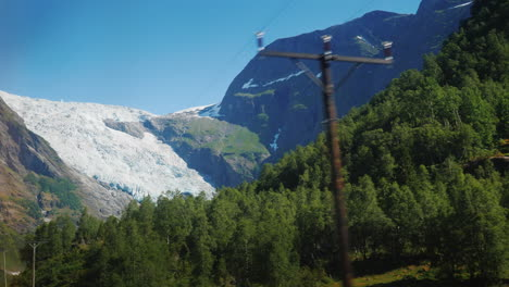 Driving-Through-The-Picturesque-Places-Of-Norway-Beyond-The-Window-Are-High-Mountains-And-A-Large-Gl