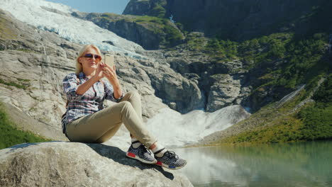 A-Happy-Tourist-Does-Selfie-On-The-Background-Of-A-Glacier-In-Norway-Traveling-In-Norway-Concept
