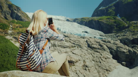Woman-Tourist-Taking-Pictures-Of-The-Glacier-Traveling-In-Norway-Concept