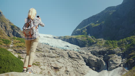 An-Active-Traveler-Woman-Stands-On-A-Rock-Photographs-A-Beautiful-Glacier-In-Norway-Journey-Through-