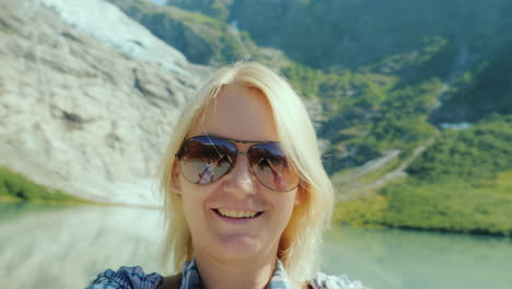 A-Woman-In-Sunglasses-Shoots-Herself-On-Video-Against-The-Backdrop-Of-The-Mountains-And-The-Glacier-