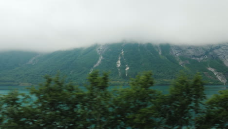 Go-In-The-Fog-Along-The-Forest-View-From-The-Car-Window-Driving-In-Poor-Visibility-High-In-The-Mount