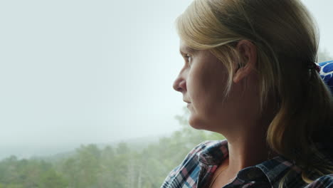A-Woman-Looks-Out-The-Window-Of-A-Bus-To-A-Forest-Covered-With-Thick-Fog-Traveling-In-Norway