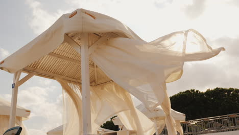 Beach-Sunbeds-With-A-Canopy-Develop-In-The-Wind-At-The-Seaside-Resort