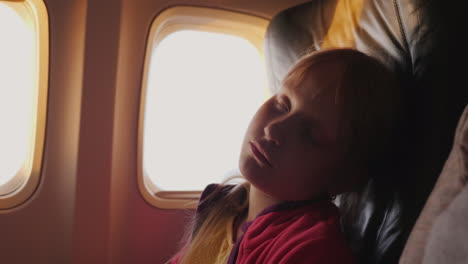 The-Little-Girl-Is-Sleeping-In-The-Cabin-Of-The-Plane-During-The-Dawn-The-Orange-Rays-Of-The-Sun-Ill