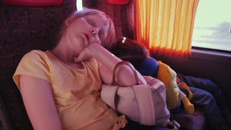 Two-Small-Tired-Girls-Sleep-On-Backpacks-In-A-Tourist-Bus