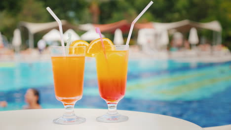 Two-Exotic-Cocktails-On-The-Background-Of-Bathing-Tourists-In-The-Pool-In-A-Large-Comfortable-Hotel