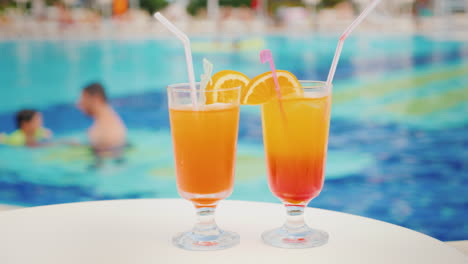 Two-Cocktails-With-Straws-On-The-Background-Of-The-Pool-The-Pool-Blurred-Contours-Father-Teaches-His