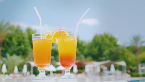 Two-Orange-Cocktails-With-Straws-And-Orange-Slices-Are-On-The-Beach-Table-By-The-Pool-Against-The-Bl