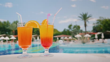 Two-Cool-Cocktails-Stand-On-The-Table-On-The-Background-Of-The-Pool-And-Palm-Trees-Paradise-And-Luxu
