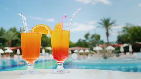 Relax-On-The-Sun-Loungers-Near-The-Pool-With-Two-Exotic-Cocktails-With-Straws-Blue-Sky-And-Green-Pal