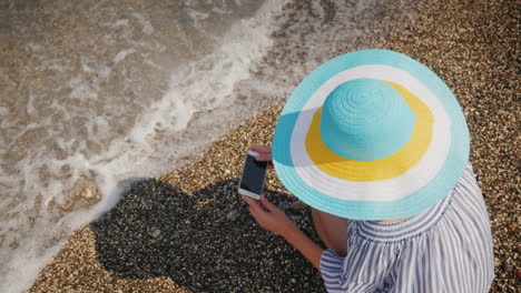 A-Woman-In-A-Summer-Hat-Sits-On-The-Seashore-Photographs-Stones-And-Surf-Woman-On-Vacation-Concept-4