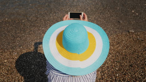 A-Woman-In-A-Summer-Dress-And-Hat-Is-Photographing-The-Surf-Woman-On-Vacation-Concept-Top-View