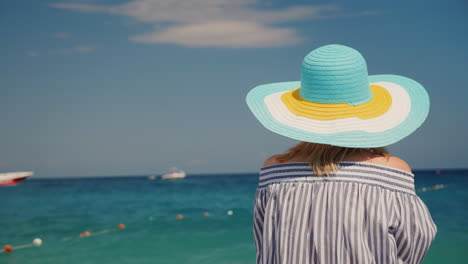 A-Woman-In-A-Hat-Admires-The-Sea-A-Rear-View-Woman-On-Vacation-Concept-4k-Video-Back-View