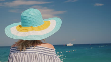 A-Woman-In-A-Hat-Looks-At-The-Azure-Sea-Dream-Vacation-Concept-Rear-View