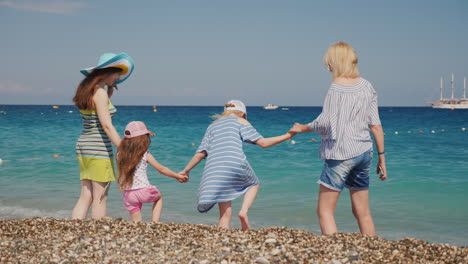 Young-Girls-With-About-Their-Young-Children-Have-Fun-On-The-Coast-Jump-On-The-Waves-Enjoy-The-Rest