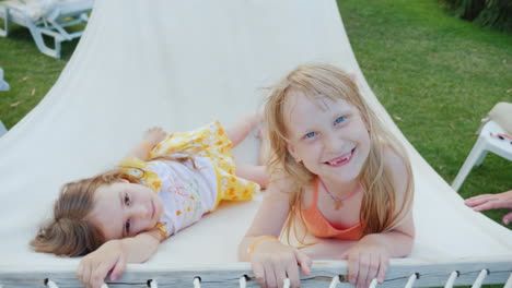 Two-Cool-Girls-Lie-On-A-Hammock-Laugh-And-Look-At-The-Camera-Top-View