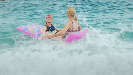 Huge-Waves-Of-The-Sea-Play-With-An-Inflatable-Mattress-A-Woman-With-A-Young-Child-Laugh-Have-Fun-On-