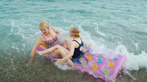 Large-Waves-Of-The-Sea-Carry-An-Inflatable-Mattress-With-A-Mother-And-A-Child-A-Fun-Ride-On-The-Wave