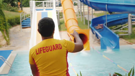 The-Rescuer-Is-On-Duty-At-The-Water-Slides-Rear-View-4k-Video
