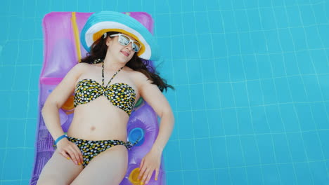 Girl-Tourist-In-A-Swimsuit-Resting-In-The-Pool-On-An-Inflatable-Mattress-In-A-Multi-Colored-Hat-And-