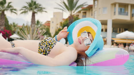 A-Pretty-Girl-In-A-Cool-Hat-And-Sunglasses-Is-Resting-On-The-Mattress-Enjoying-The-Rest-In-The-Pool