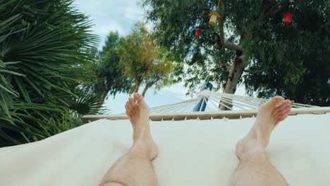 A-Man-Is-Resting-In-A-Hammock-A-First-Person-View-In-The-Frame-Only-The-Legs-Are-Visible-4k-Video