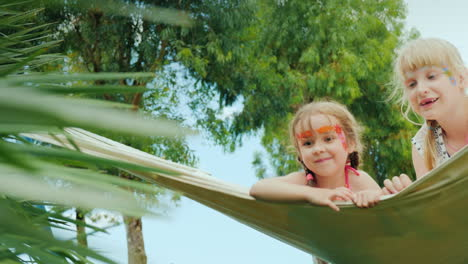 Funny-Children-With-Painted-Faces-Ride-On-A-Hammock-On-The-Territory-Of-The-Hotel-On-The-Beach