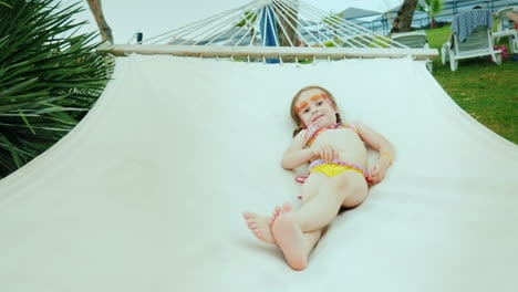 A-Small-Girl-In-A-Swimsuit-And-With-Two-Pigtails-Sunbathing-On-A-Beach-Hammock-And-A-Resort-Hotel