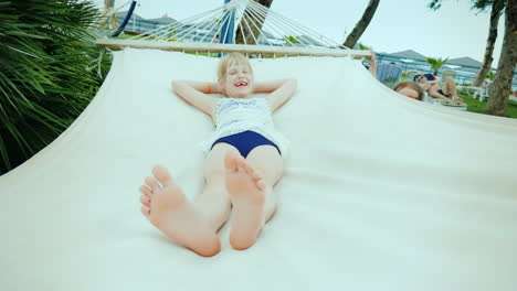 A-Little-Girl-Shakes-Her-Older-Sister-On-A-Hammock-Having-Fun-During-The-Summer-Holidays