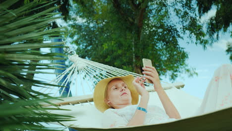 Young-Woman-Resting-In-A-Hammock-Using-A-Mobile-Phone-Connection-On-Vacation-Concept-4k-Video