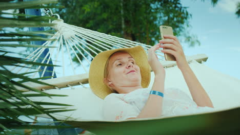 Portrait-Of-A-Woman-On-Vacation-Lies-In-A-Hammock-Uses-A-Smartphone-4k-Video