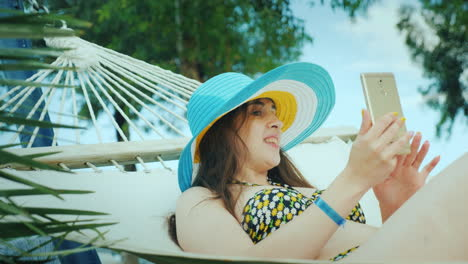 A-Cute-Brunette-In-A-Wide-Brimmed-Hat-And-In-A-Bikini-Enjoys-Relaxing-In-The-Seaside-Resort-Reading-