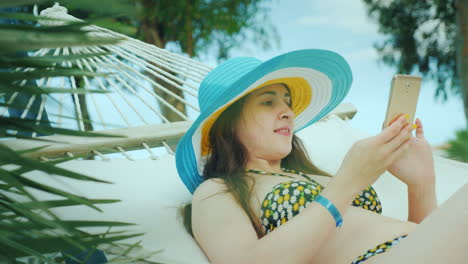 A-Young-Dark-Haired-Girl-In-A-Bikini-And-Wearing-A-Bright-Wide-Brimmed-Hat-Is-Resting-On-A-Hammock-A