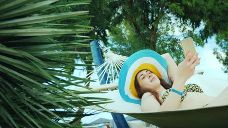 Enjoy-The-Rest-And-Be-Always-In-Touch-With-Friends-A-Girl-In-A-Cool-Hat-And-A-Bathing-Suit-Sunbathin