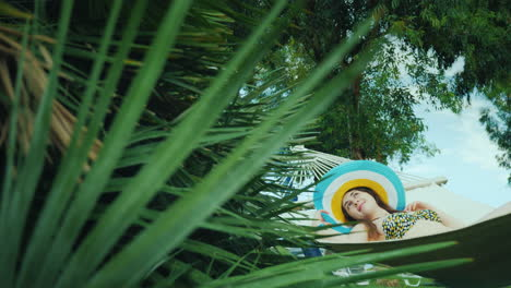 Away-From-Civilization-A-Young-Woman-Relaxes-On-A-Hammock-Around-The-Green-Palm-Trees-The-Blue-Sky