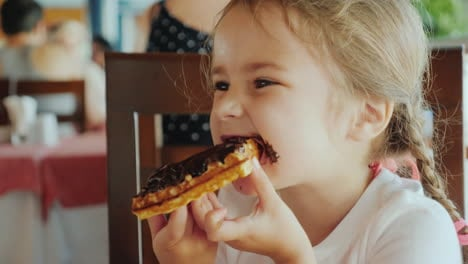 The-Portrait-Of-A-Little-Girl-With-Two-Pigtails-Which-Eats-A-Chocolate-Waffle-All-Smeared-With-Sweet