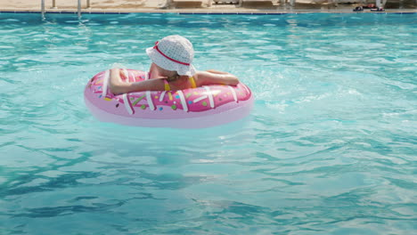 A-Funny-Little-Girl-In-A-Panama-Skates-On-An-Inflatable-Circle-In-A-Large-Pool-In-A-Hotel-On-The-Sea