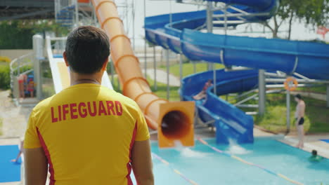 A-Man-In-A-Yellow-T-Shirt-With-An-Inscription-On-The-Back-Of-The-Rescuer-Watching-Children-Roll-On-T