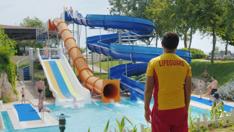 Rear-View---The-Rescuer-Watches-People-On-The-Water-Slides-Working-In-The-Water-Park